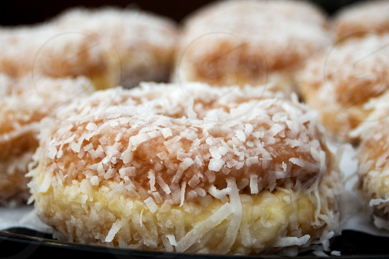 Coconut encrusted doughnut on donut tray photo