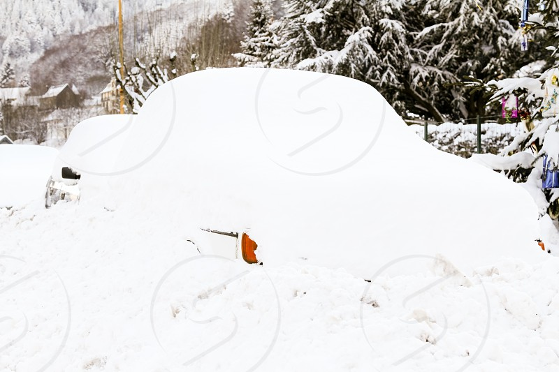 snowed under : a car somewhere in France but it could be anywhere completely recovered with fresh snow. You can only a bit of body paint and an indicator.  PS : no model release needed. photo