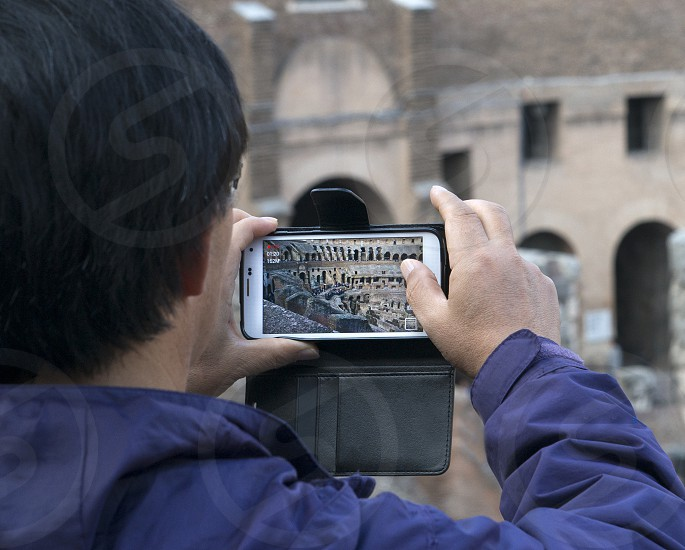 Person taking picture on phone of The Colosseum or Coliseum in Rome photo