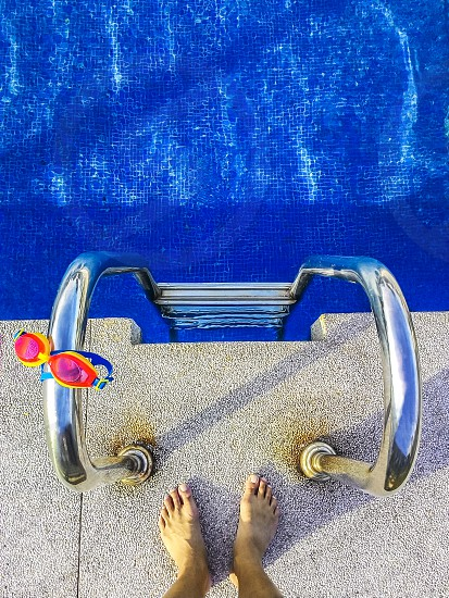 Top view of human feet standing on edge of outdoor swimming pool photo