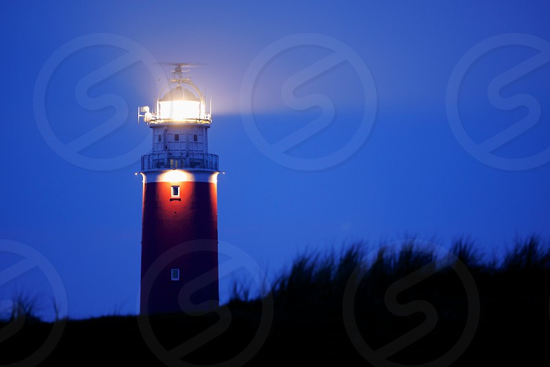 photography of a red and white lighthouse during night photo