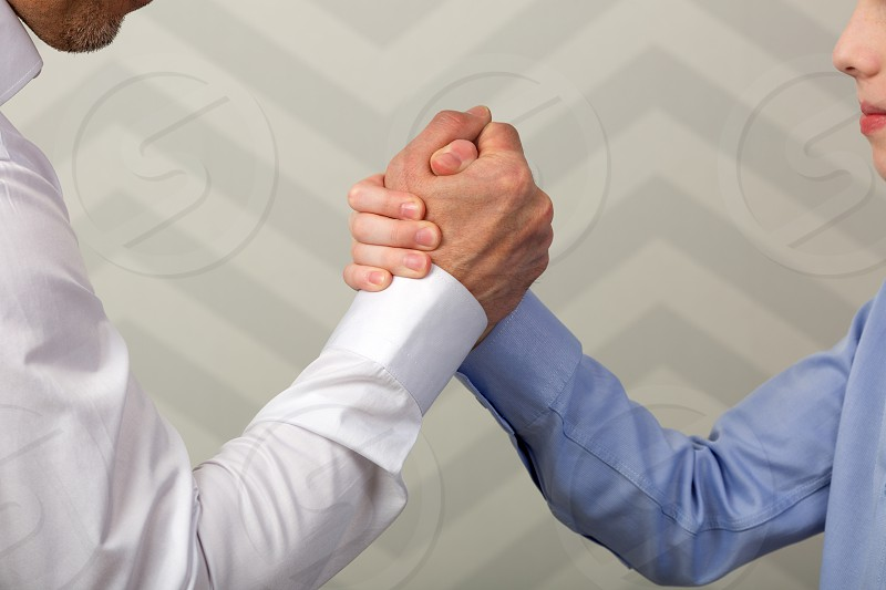 Father and son with hands in strong handshake or during arm wrestling competition photo
