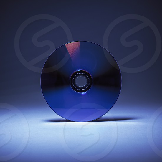 Simple composition closeup view of a compact disk in blue background. photo