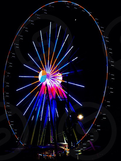 night view of color lighted ferris wheel photo