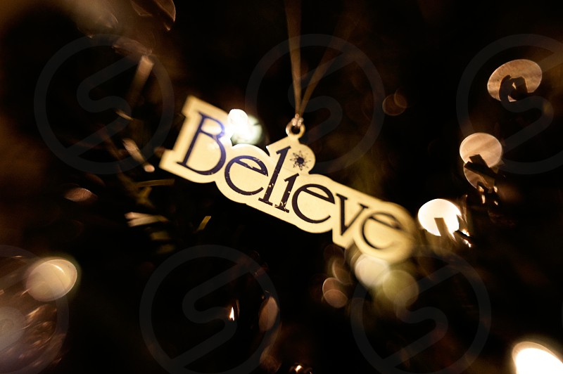 Believe holiday ornament on a Christmas tree photo