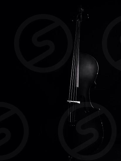 cello standing in dark room photo