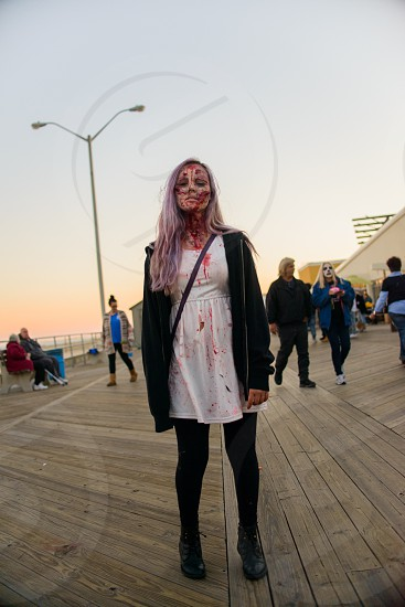 woman in white mini dress black leggings and black jacket standing in pathway with bloody face photo