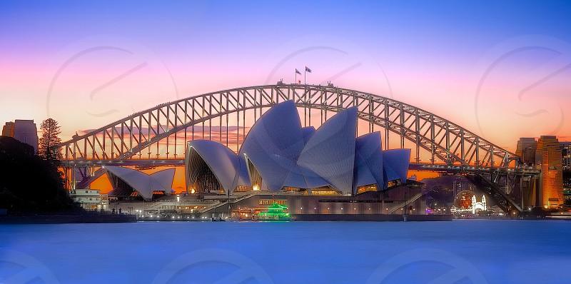 Sydney Opera House in front of the Sydney Harbour Bridge during sunset. sydney australia harbour harbour bridge water sunset calm clear  photo