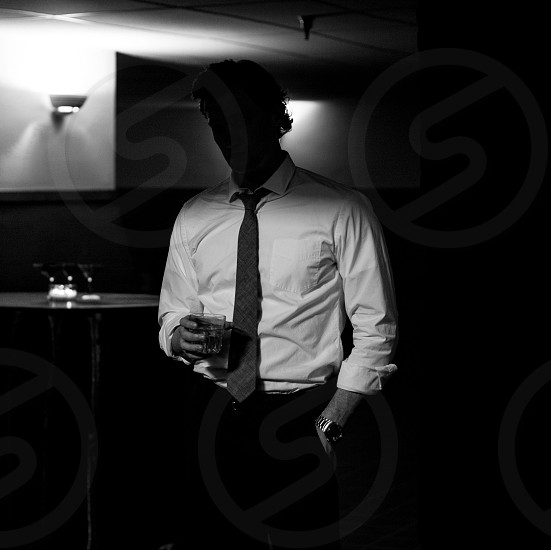 man in white long sleeved shirt standing holding glass photo