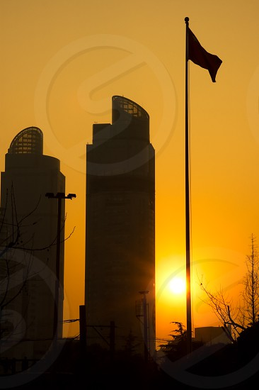 shanghai twins towers over an orange sky during sunset photo