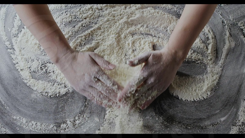 The cook's hands in a fresh flour are moving powder in a pile on a wooden table . Slow motion Full HD video 240fps 1080p. Process preparing of homemade pastry. Top view. photo