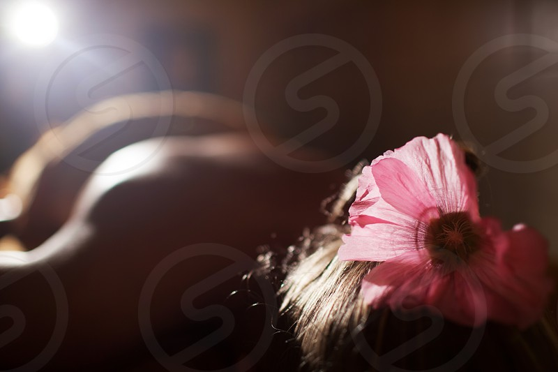 Relaxed woman with pink flower in hair lying at beauty spa salon and waiting for treatments photo