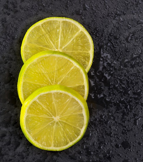 Fresh lima slices with water drops on black slate stone background photo