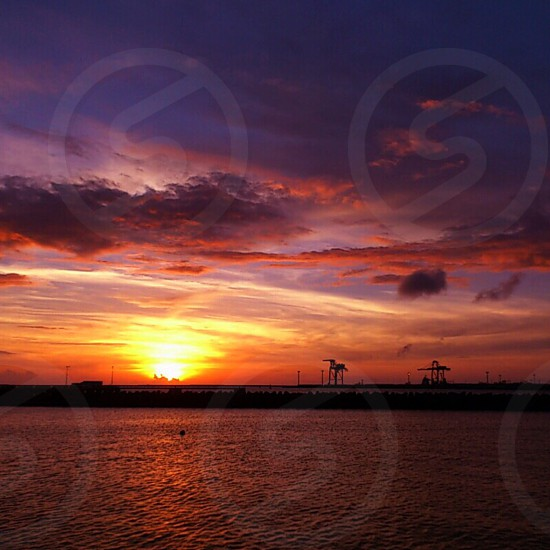 silhouette of buildings across body of water during orange and yellow sunset photo