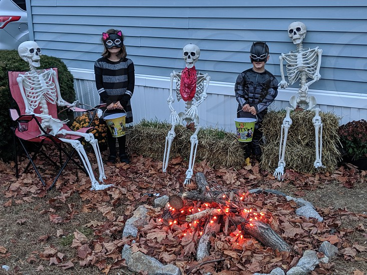kids in coatumes by skeleton decorations photo