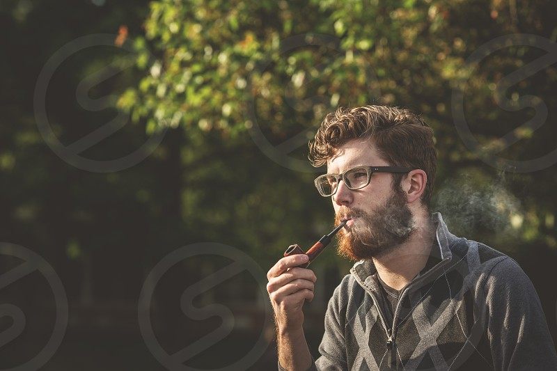 man smoking on pipe photo