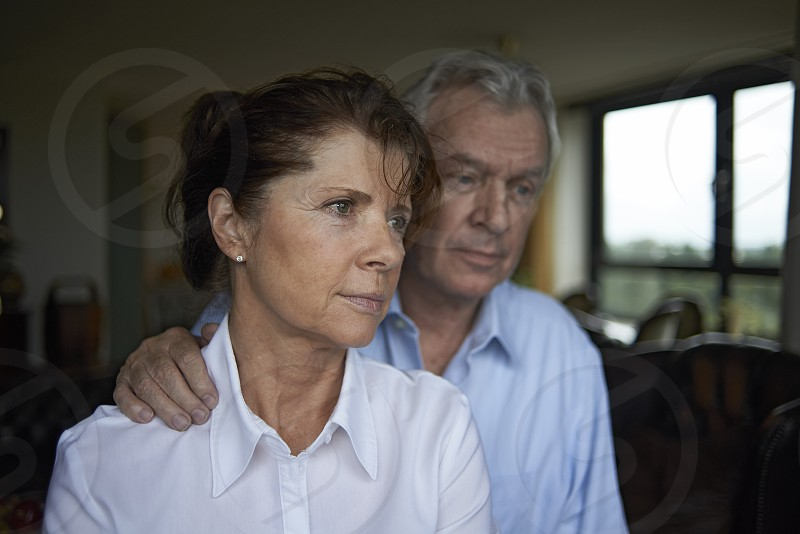 Elderly couple in their home in a loving embrace together giving each other comfort photo