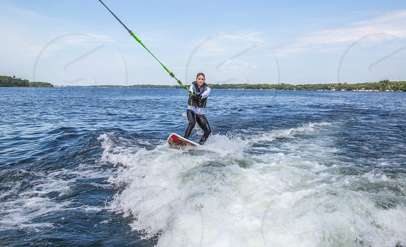 Woman riding surfboard on the lake photo