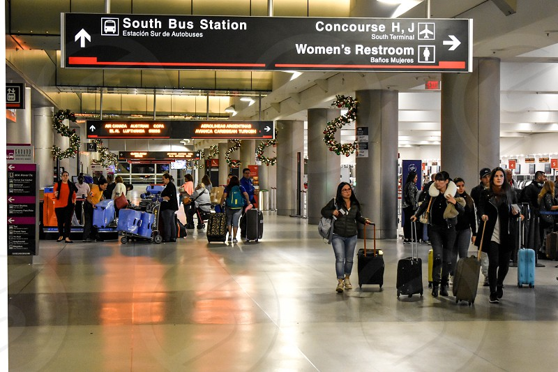 Miami Florida. January 05 2019. People walking with suitcases and South Bus station sign at Miami International Airport. photo