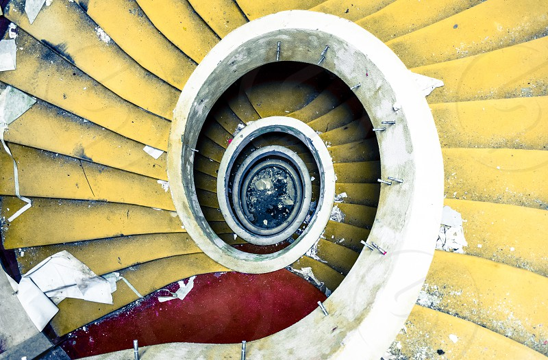 degraded yellow spiral stair case photo
