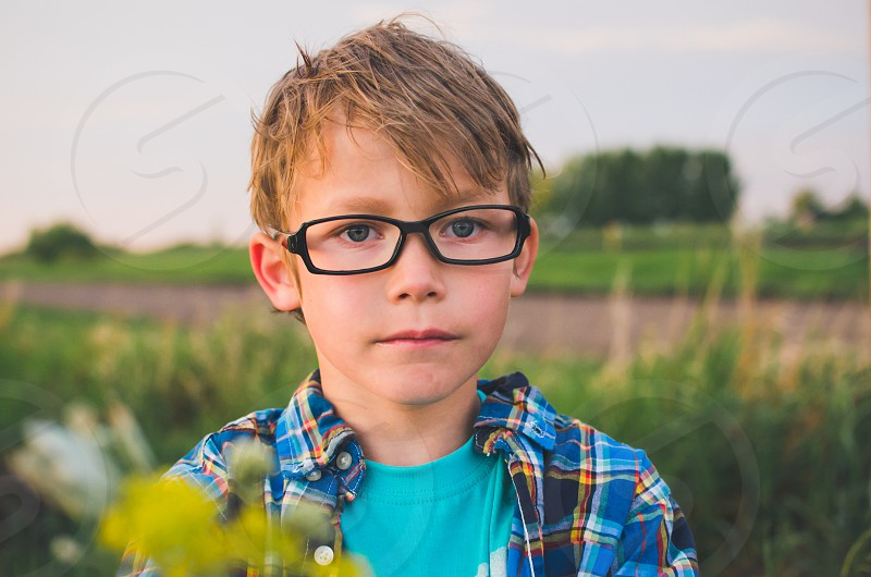 Boy in glasses wearing plaid shirt in field holding flowers. photo
