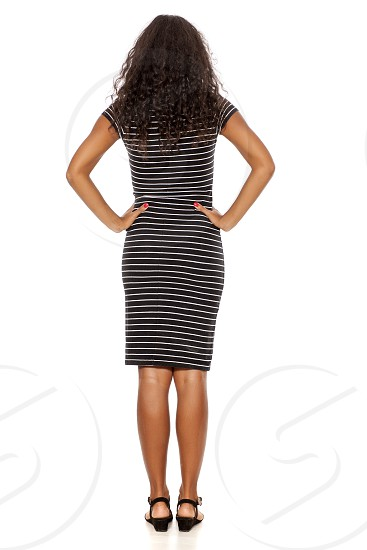 Back wiew of young and pretty dark skinned woman posing on white background photo