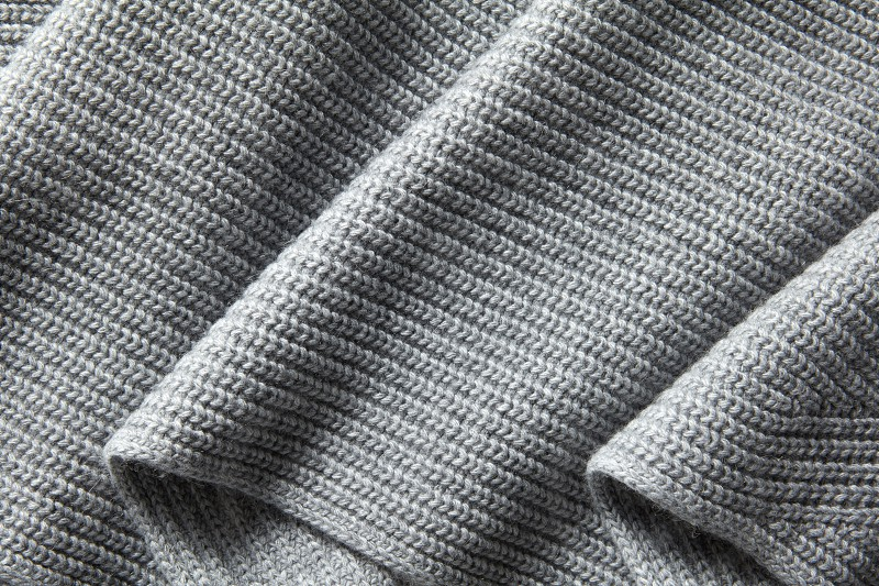 Gray wool knitted fabric folds. Natural draped knitted texture photo