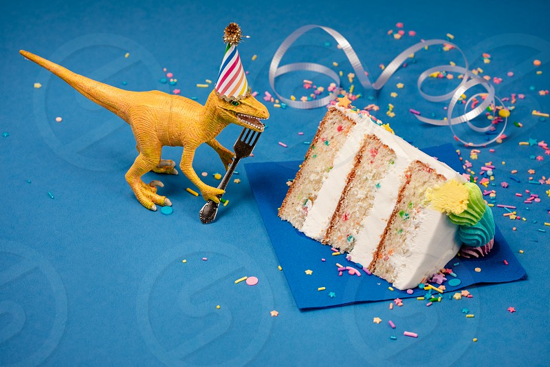 Toy Dinosaur holding a fork next to a slice of birthday cake on a blue background. photo