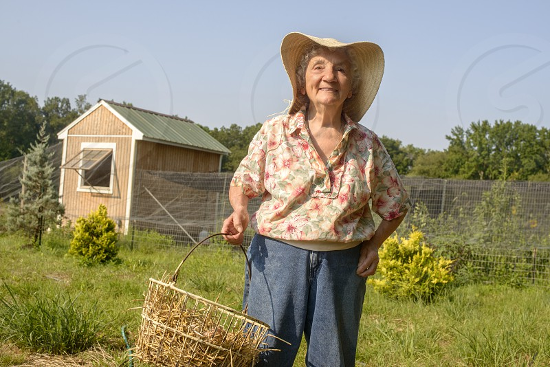 smiling woman wearing a gardening hat holding a basket standing in a field surrounded by a fence with wood shed in the distance photo