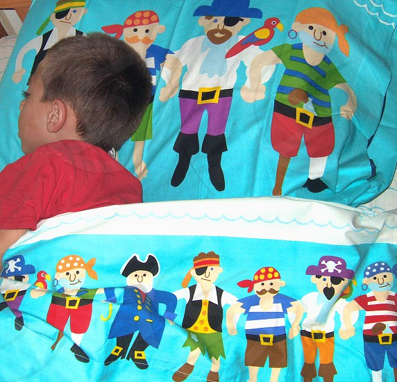 Little boy asleep in colorful pirate sheets photo