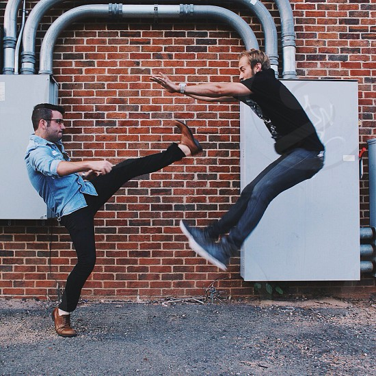 man pretending to kick another man in the stomach photo