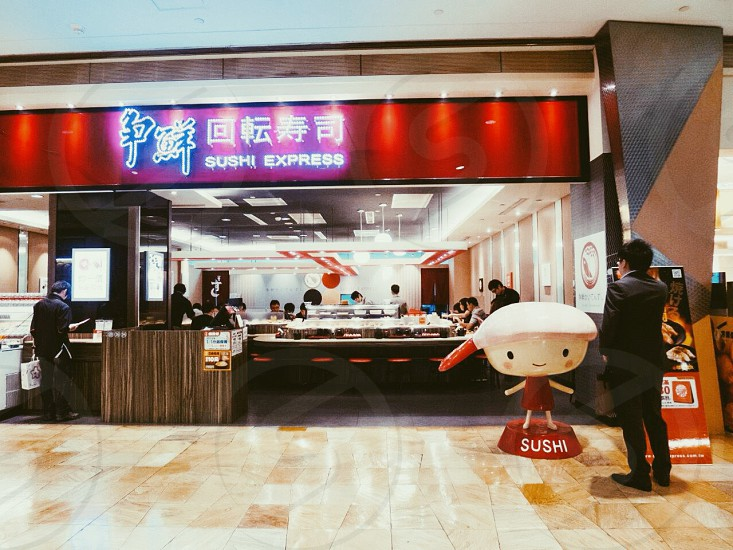 man standing in front of sushi express photo