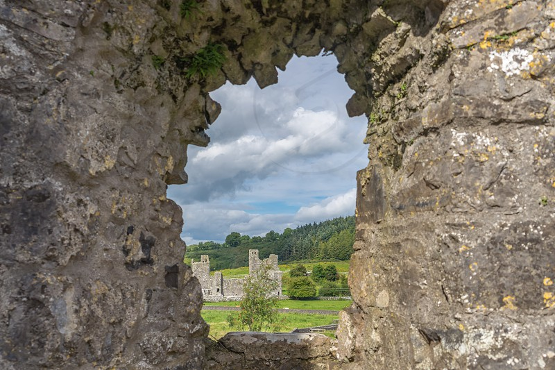 A view through a hole in a wall at an old monastery in Ireland. photo