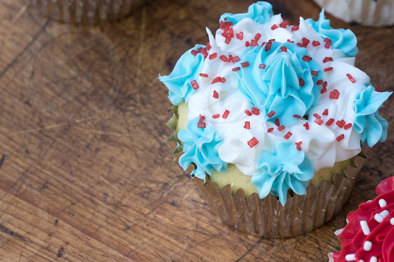 A frosted and sprinkled cupcake on a rustic wood table photo
