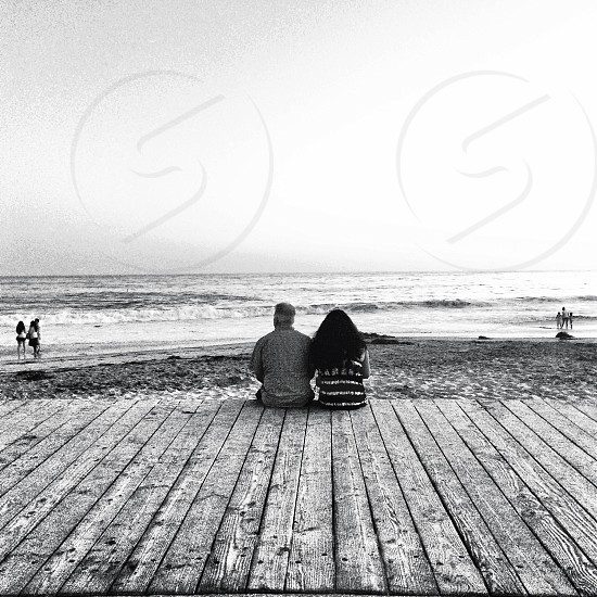 grayscale photography of two persons sitting beside the sea photo