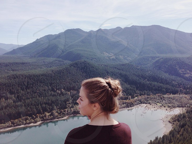 brunette woman with her hair in a bun wearing black shirt standing at op of hill over looking blue lake and dark green forested mountain ranges photo