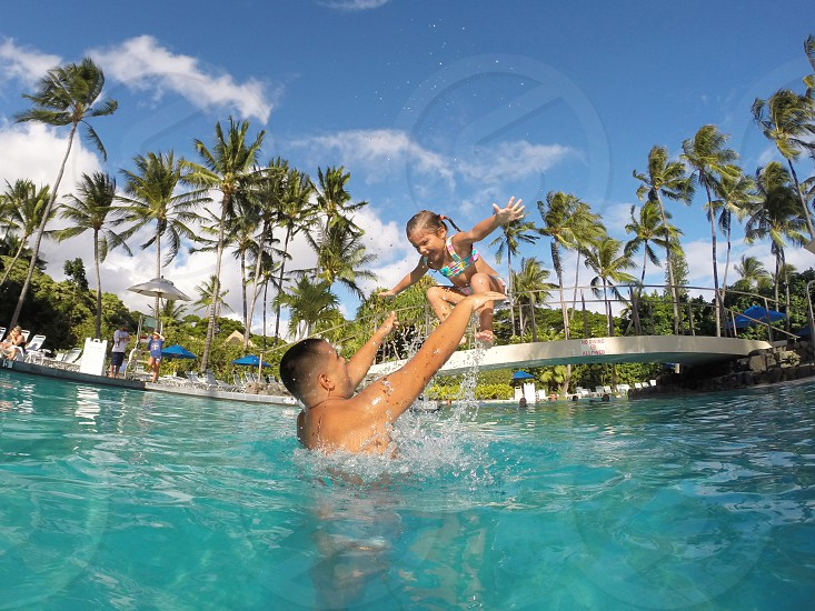 topless man catching girl in one piece swimsuit jumping to the in ground swimming pool photo