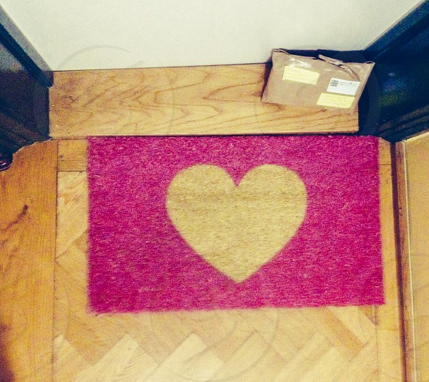 pink and brown heart print door mat on the floor beside brown delivery package photo