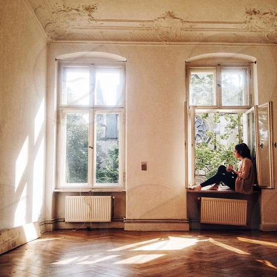 woman sitting on windowsill in empty room with wood flooring photo