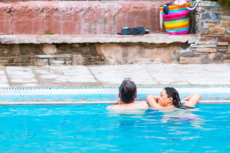 man and woman on swimming pool leaning on pool railings photo