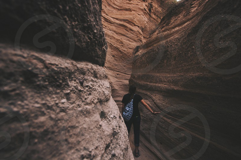 photo of person on canyon pathway wearing black outfit with blue cross body bag photo