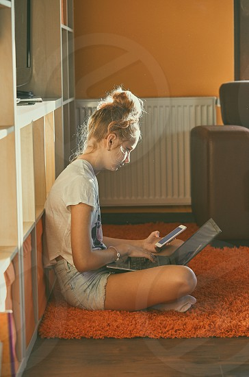Young woman using portable computer and mobile phone sitting on a floor learning online at home. Candid people real moments authentic situations photo
