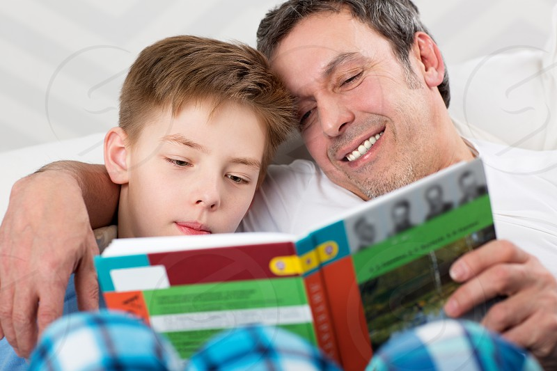 Father and son reading a book. Careful dad helping child to learn new things photo