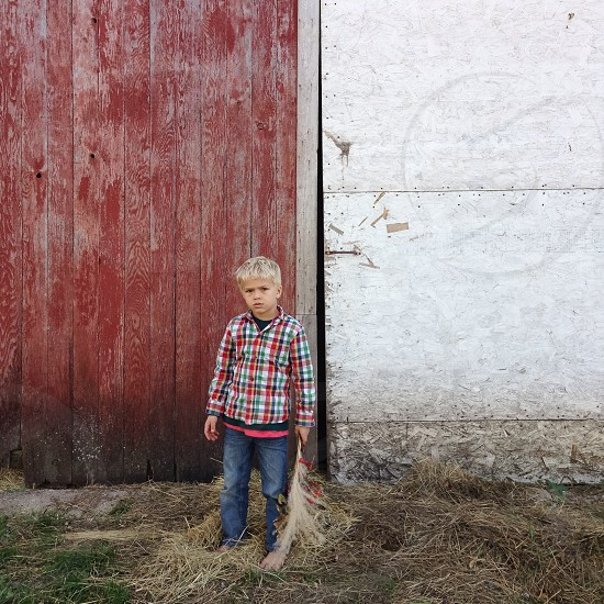 Blonde Boy Wearing Flannel Shirt Standing in Front of Red Wood Wall photo