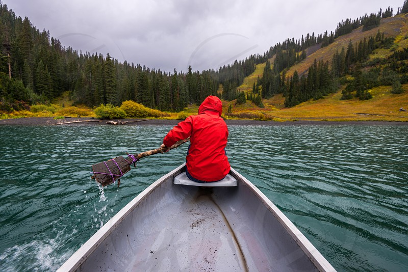person in red hoodie jacket riding on row boat photo