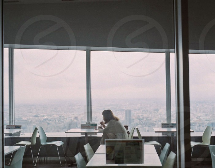 woman eating alone in the table with city aerial view  photo