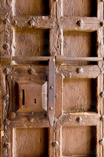 aged medieval wooden door lock keyhole with square shapes photo