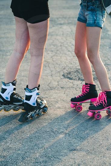 Teenage girls having fun rollerskating spending time together on summer day photo