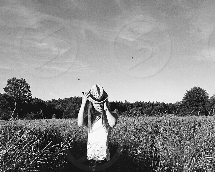 Woman with hat staying in the field photo