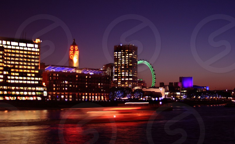 Boats rush past the colorful city lights near the London Eye on the Thames River at sunset. photo